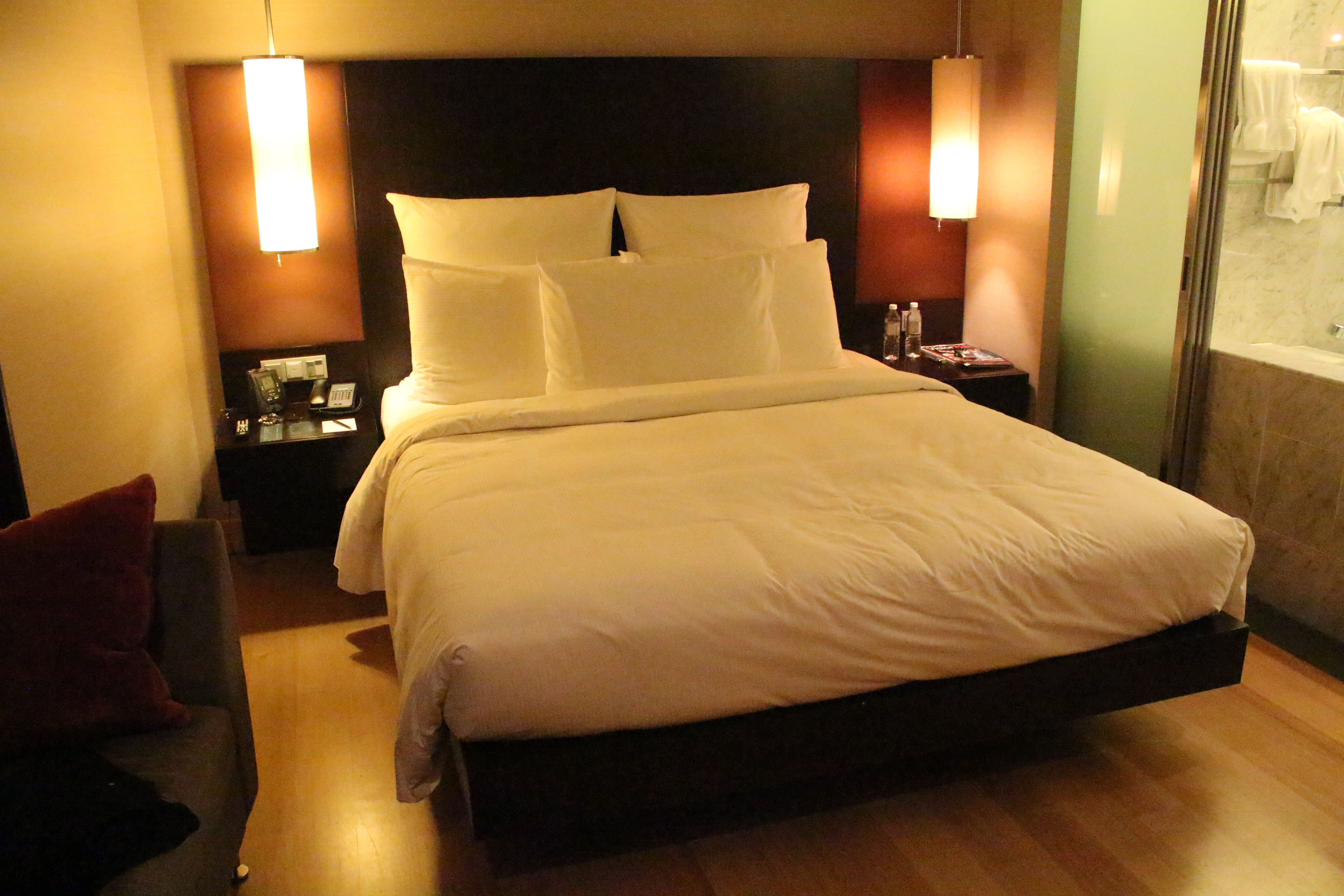 Hotel room at the Hilton in Kuala Lumpur with a king sized bed dressed in white linen.