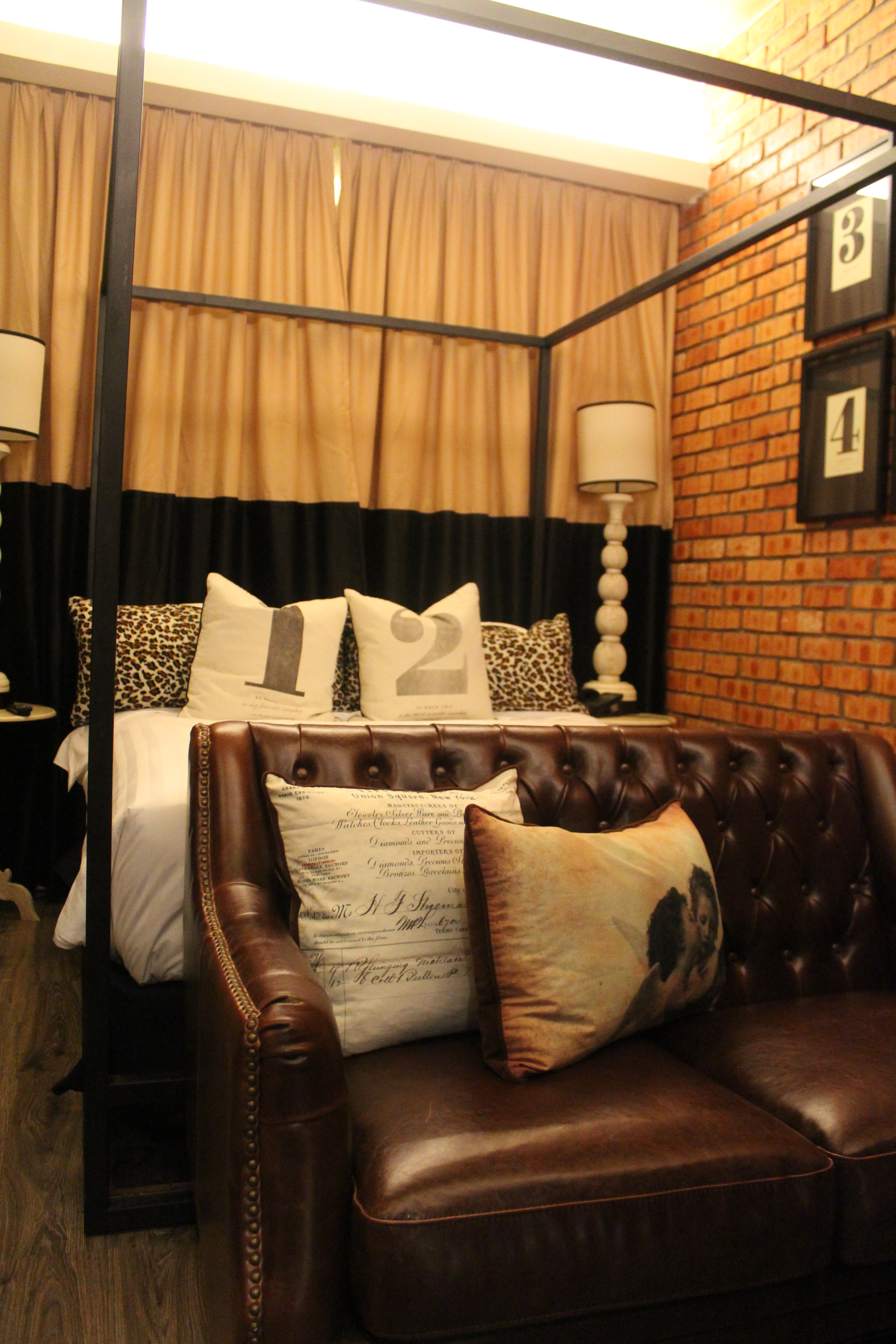 bedroom with a modern four poster bed decorated in a New York apartment style with exposed brick work, a brown leather sofa at the foot of the bed and animal print cushions