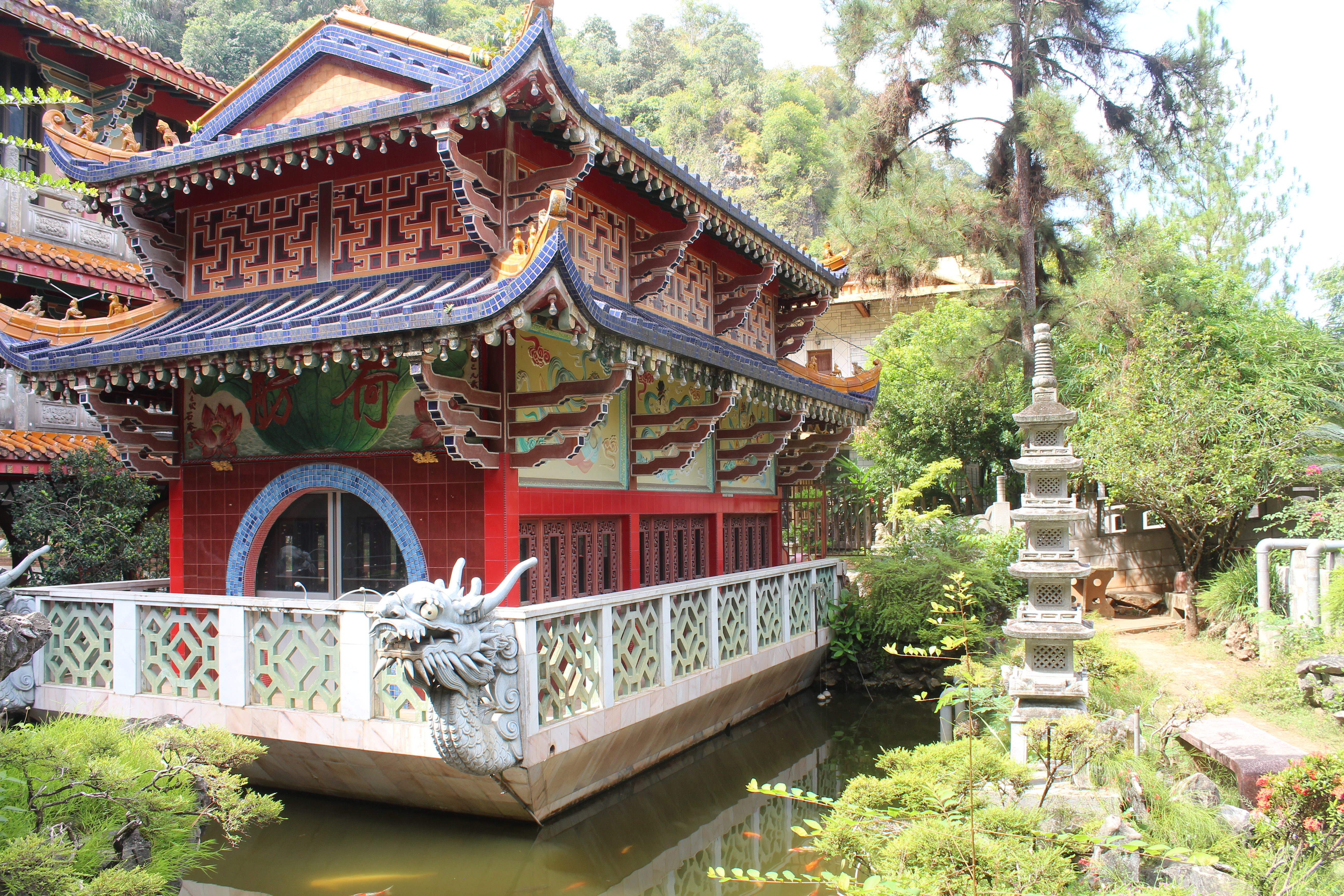 temple coloured mainly with red and purple with a pergola roof set in a small body of water with a larger temple just visible in the background