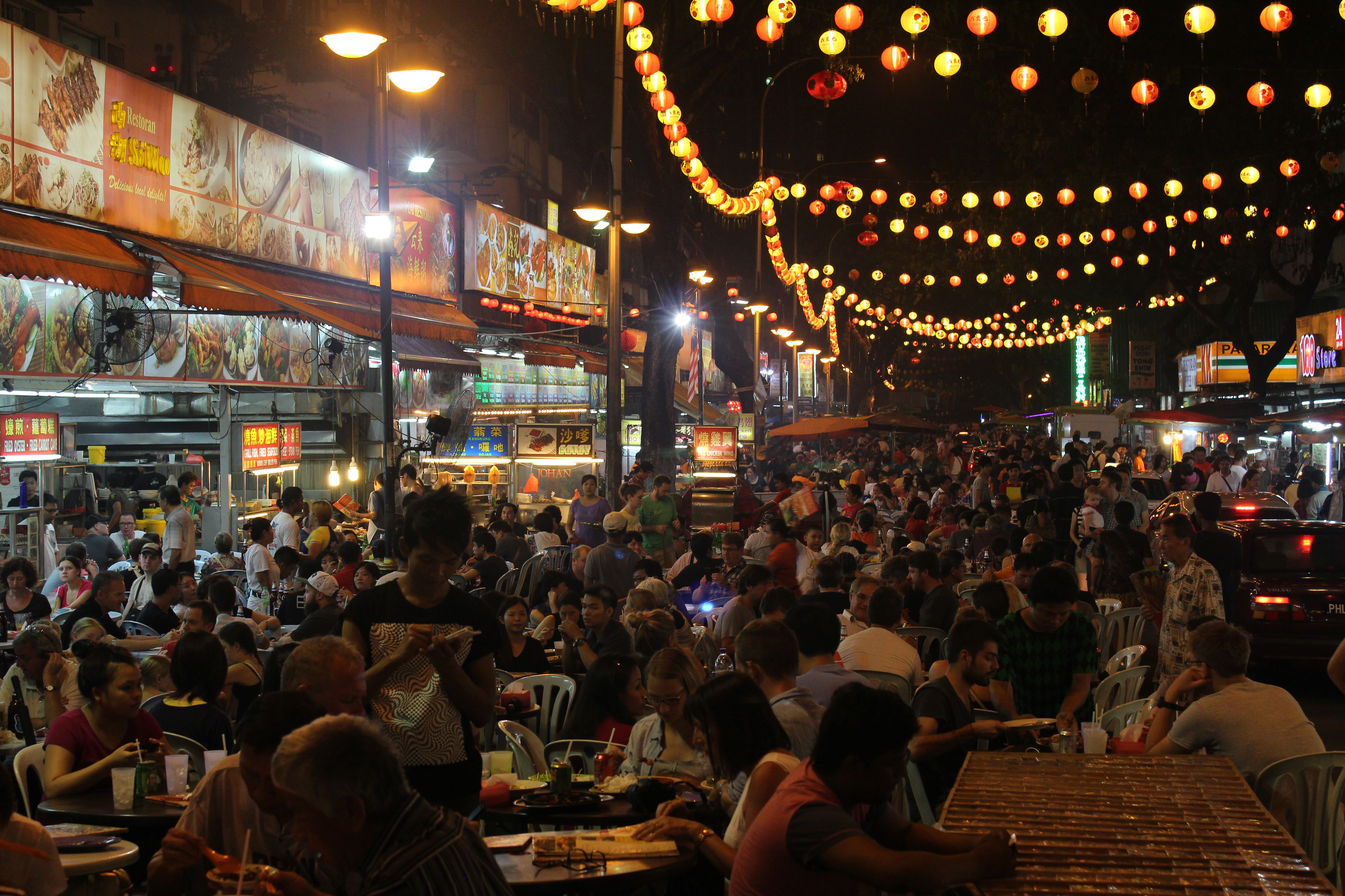 Very packed street full of food stalls and with lights strung across the street coloured red, yellow and orange.