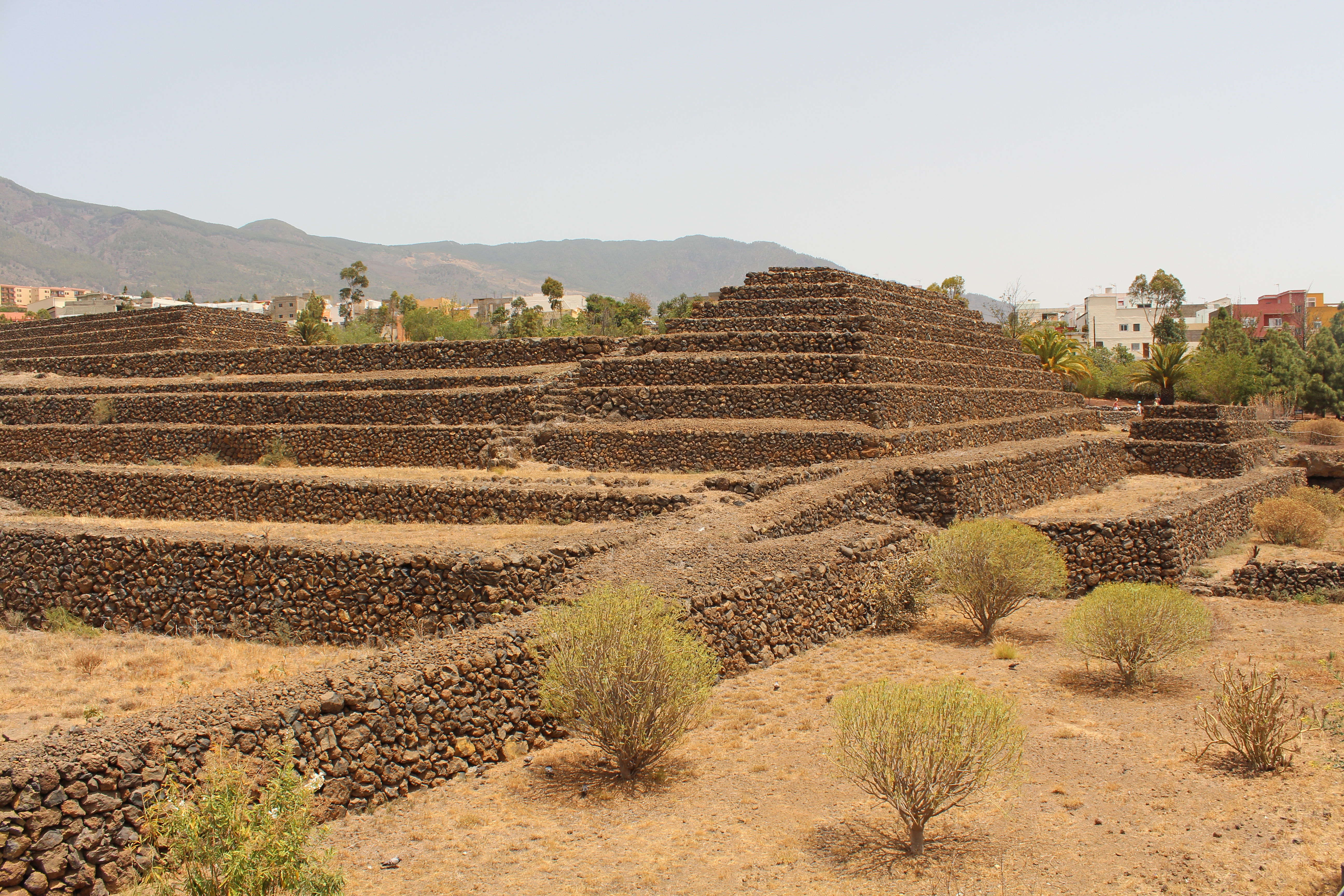 Stone rectangular pyramid set amongst a barren landscape but close to civilisation with houses just visible in th background.