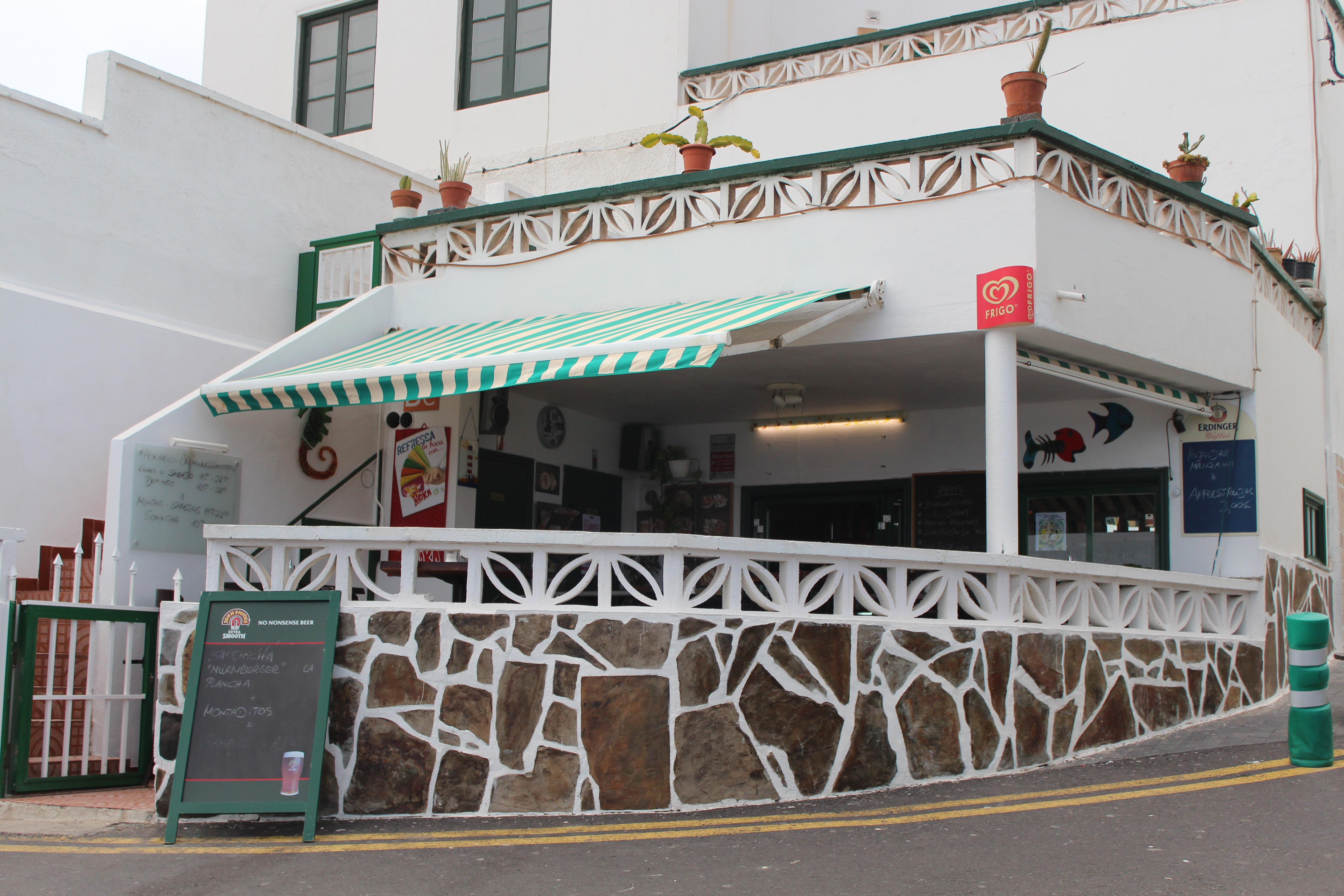 A small white washed cafe on the corner of a quiet road with a green and white striped awning.