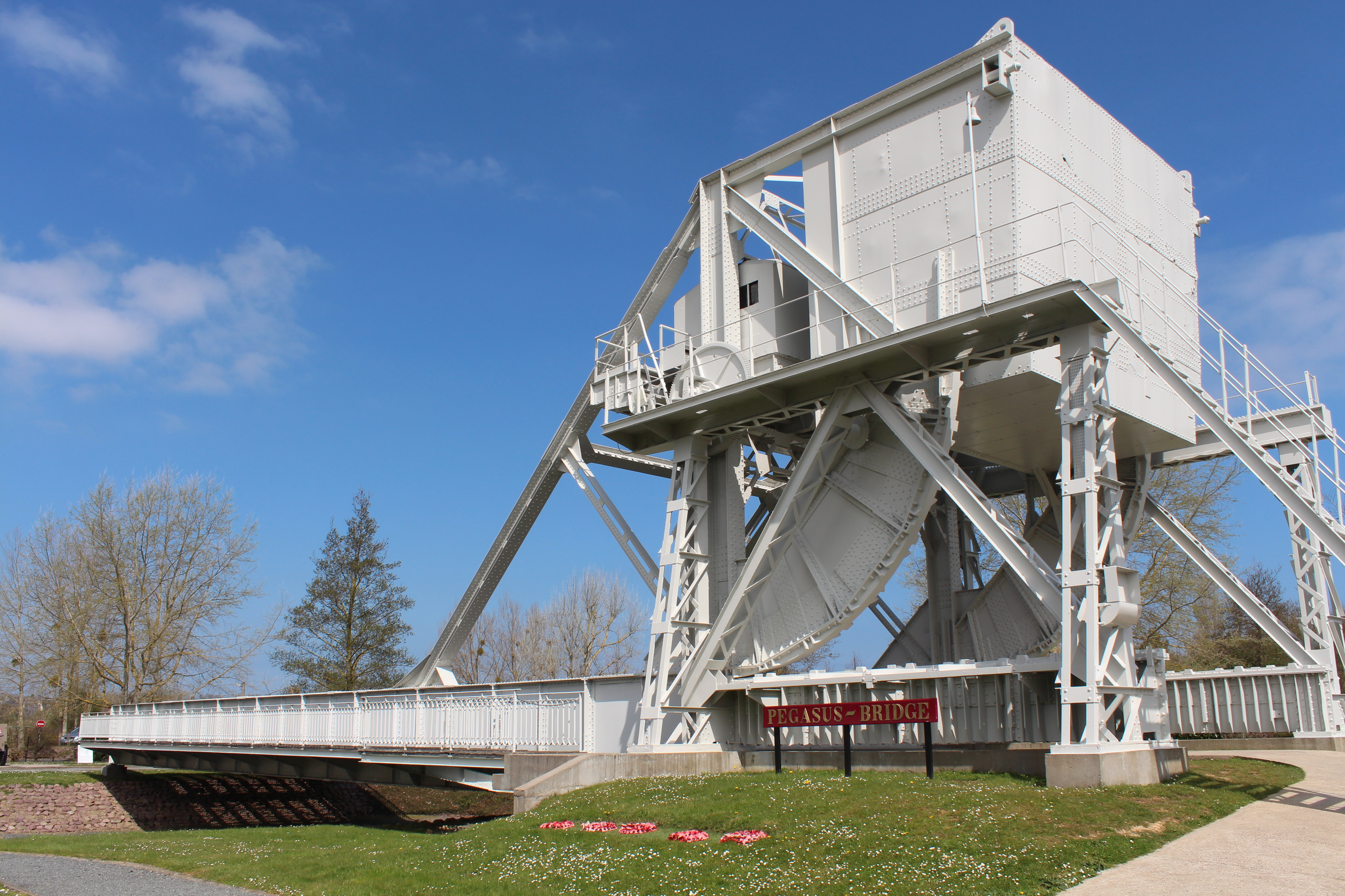 Pegasus bridge is a metal construction painted white and at one end there is an industrial box like building perched about 10 meters above the ground.