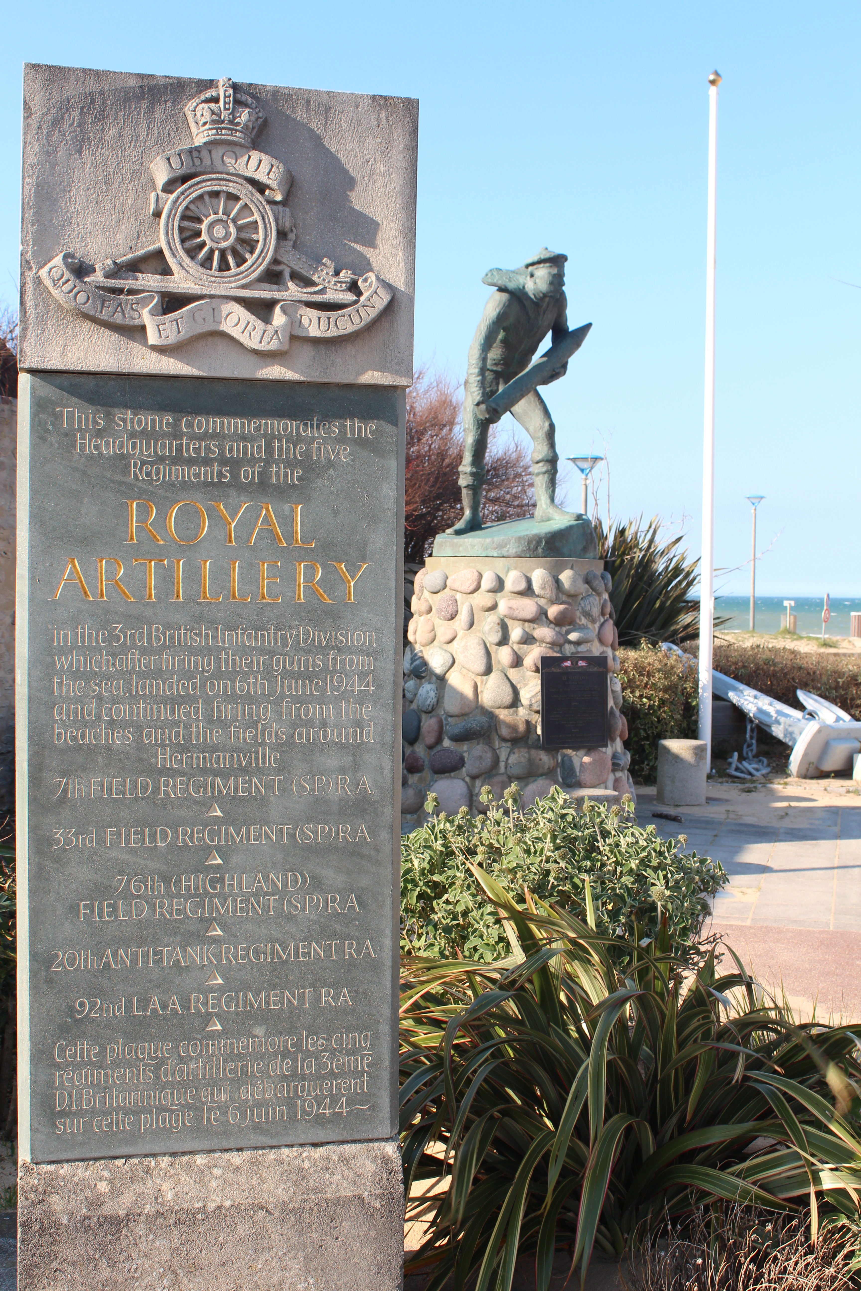 A memorial at Sword beach for the Royal Artillery with a bronze statute of a soldier in the background which has turned a shade of green.  The beach is just visible to the right of the picture.