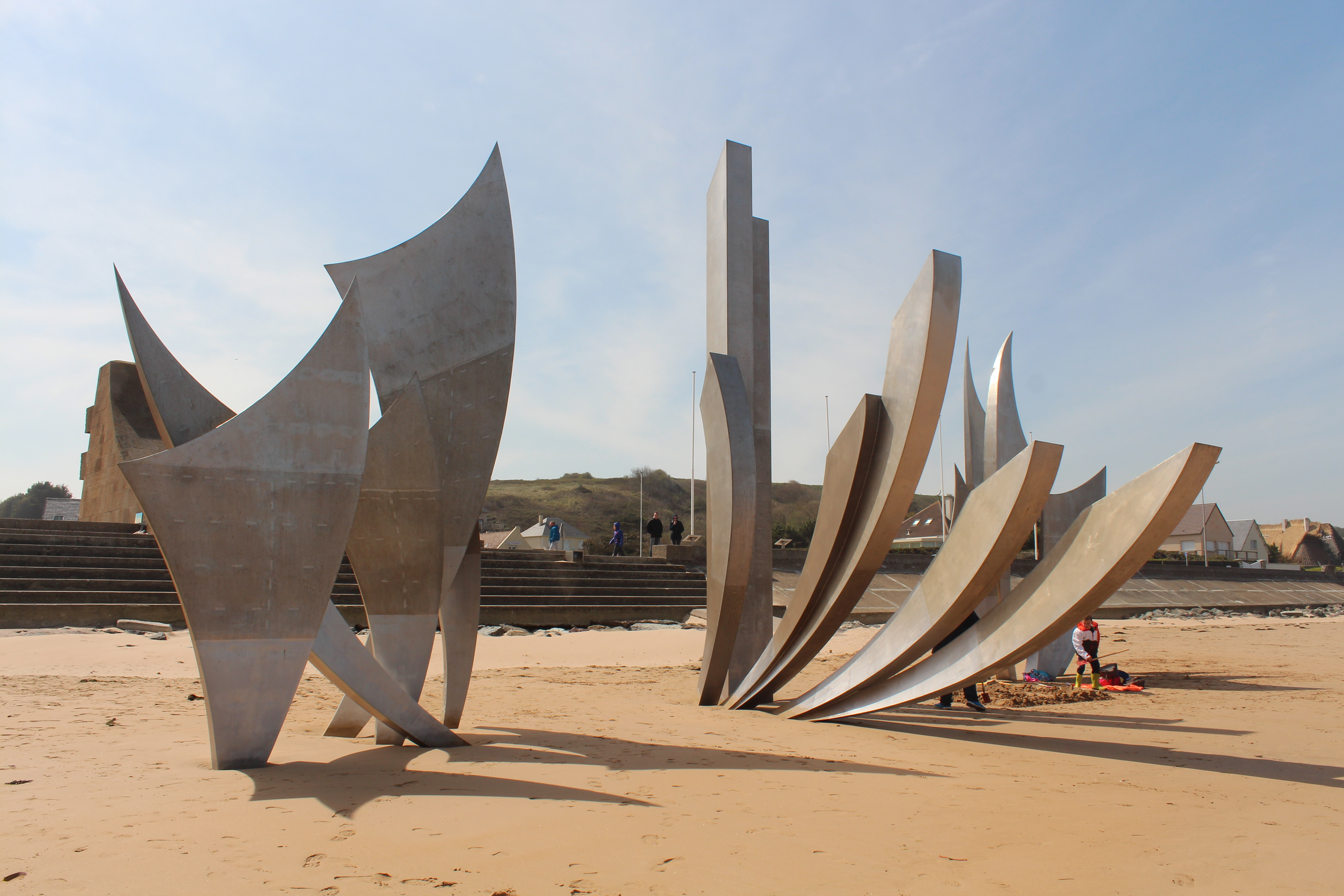 A memorial at Omaha beach which appears to shards rising from the sand.  There is a gap between the shards wide enough for several people to walk through.  A family is having a picnic underneath to the right.