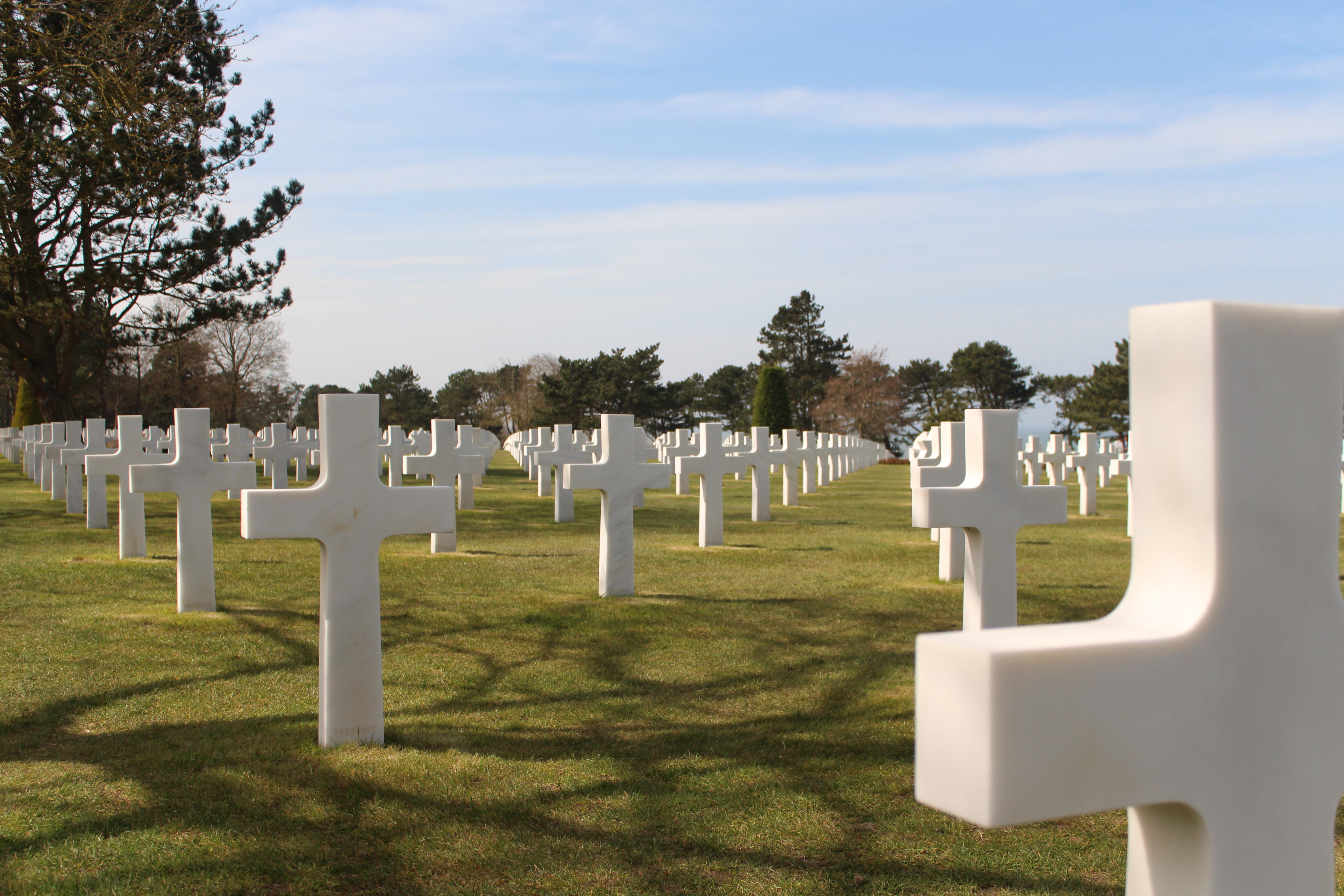 American cemetery showing neat diagonal rows of white crosses on a freshly mown lawn.