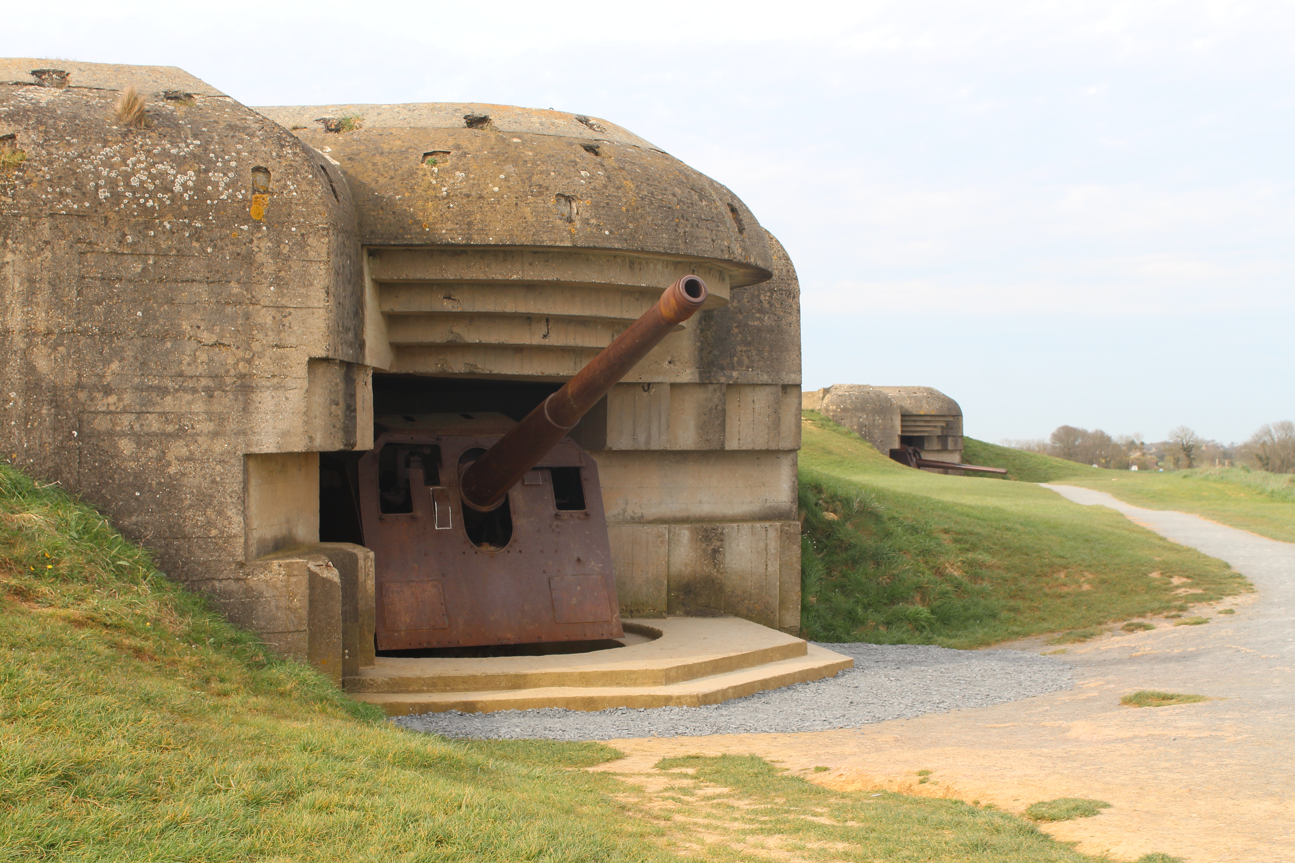 German battery at Longues Sur Mer showing a large rusty gun set in amongst concrete defences.