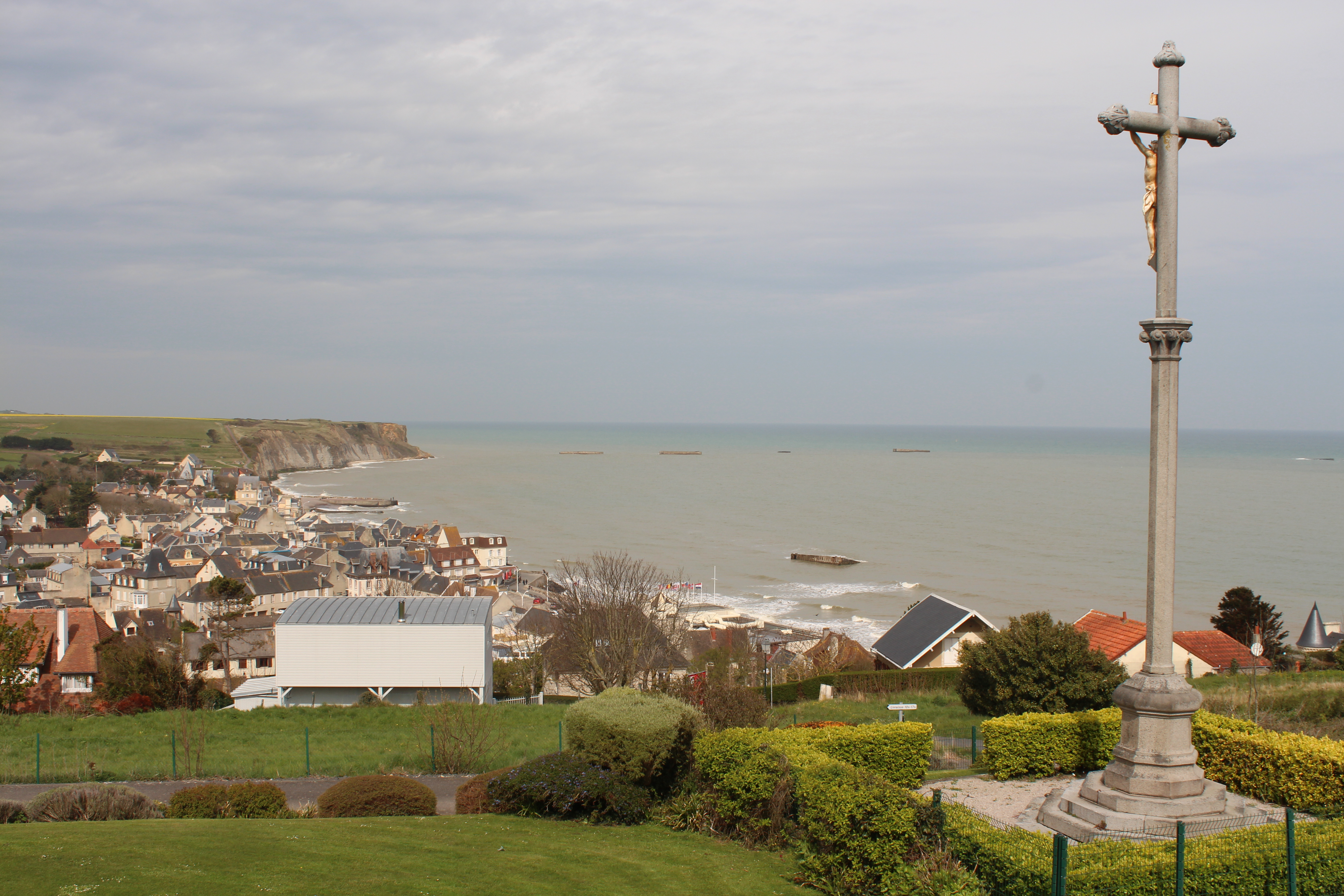 View from Arromanches museum wit a cross int he foreground looking down onto the town and sea below.