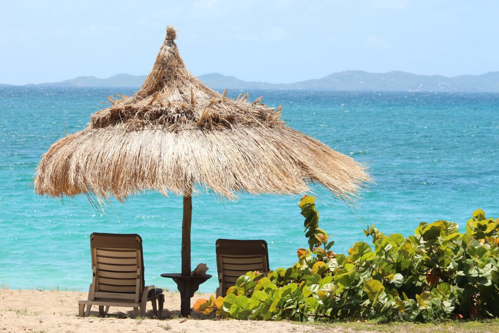 Two sun loungers resting in the sand under a straw parasol at Bequia Beach Hotel.  Showing green foliage in the foreground and with the turquoise sea in the background glistening in the sun.