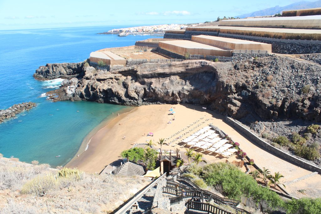 The golden sandy cove at The Ritz-Carlton Abama Tenerife with the turquoise sea to the left and banana planatation above.