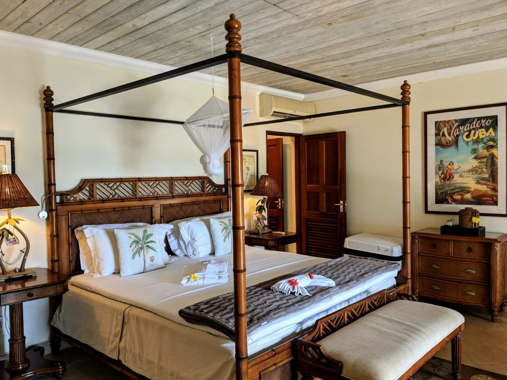 Bedroom at Bequia Beach Hotel.  A large four poster bed with mosquito net hanging tied up in the centre, quirky furnishings including palm tree cushions, a vintage Varadero Cuba poster and a little seat just at the foot of the bed.