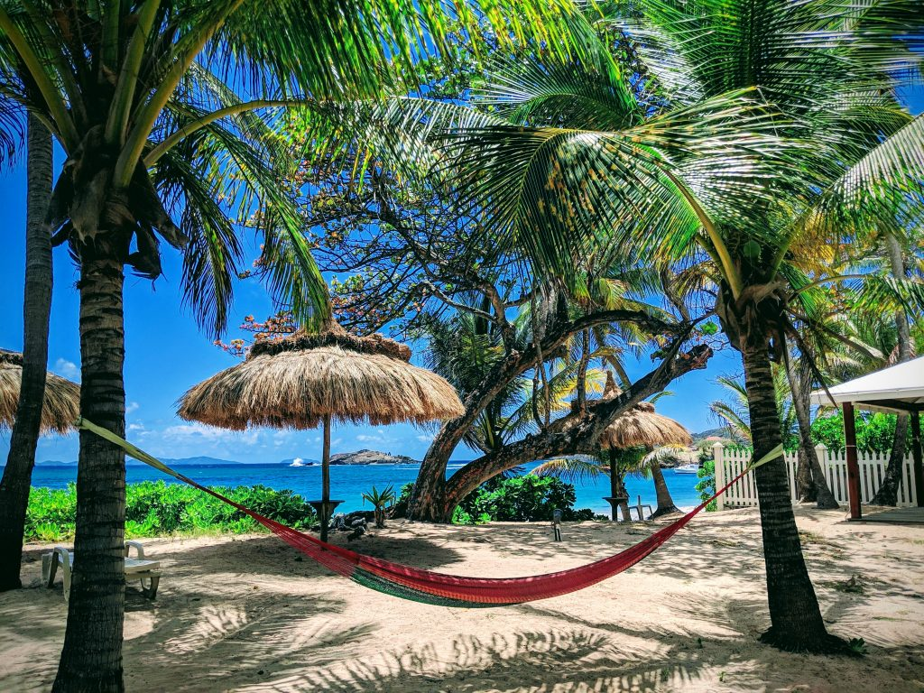 A relaxing scene at Bequia Beach Hotel showing a red hammock strung between two palm trees with straw umbrellas just behind and the beautiful blue sea in the background.
