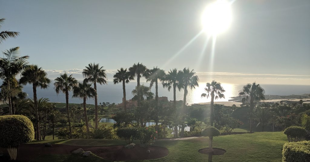 Sunset from Kabuki at the Ritz-Carlton Abama in Tenerife.  Tropical grounds with palm tress and the gold course immediately in front with the hotel down the hill in the mid distance and the sea in the background.  The sun is a golden ball of light shining down onto the ocean.