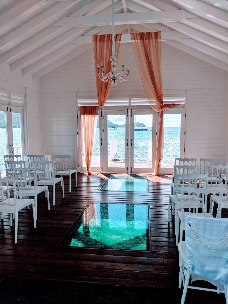 A wedding chapel at Sandals Grande St Lucia perched on the end of a secluded pier.  each side has windows which can be opened and look directly out to sea and the floor has two large glass panels which look down into the sea below.  There is a crystal chandelier at the end and peach voile framing the large window.