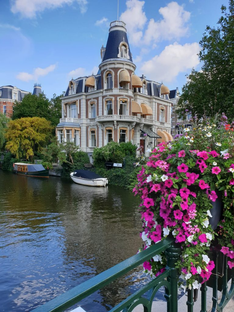 A grand building which looks like a chateau on a prominent corner plot overlooking the Amsterdam canal with some beautoful bring pink and white flowers in the foreground cascading over the bridge railing.