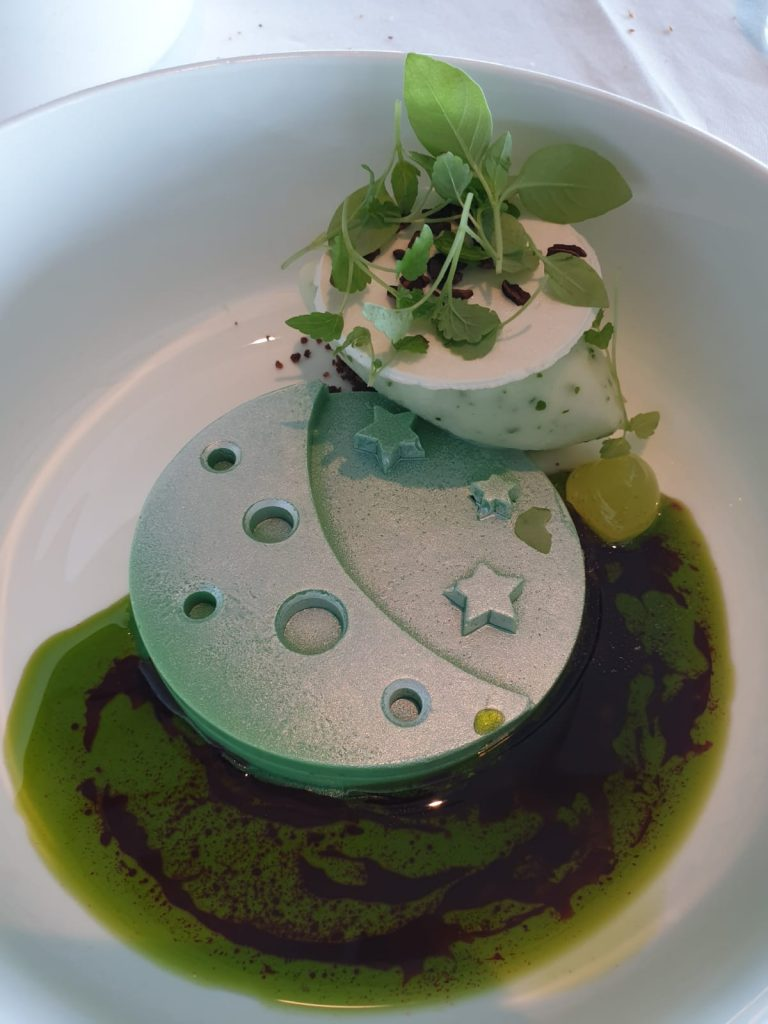 A dessert which is on vaious shades of green and has a round white chocolate central feature topped with cut outs of the moon and stars, surrounded by green jus, lime and mint, sorrel and basil side.