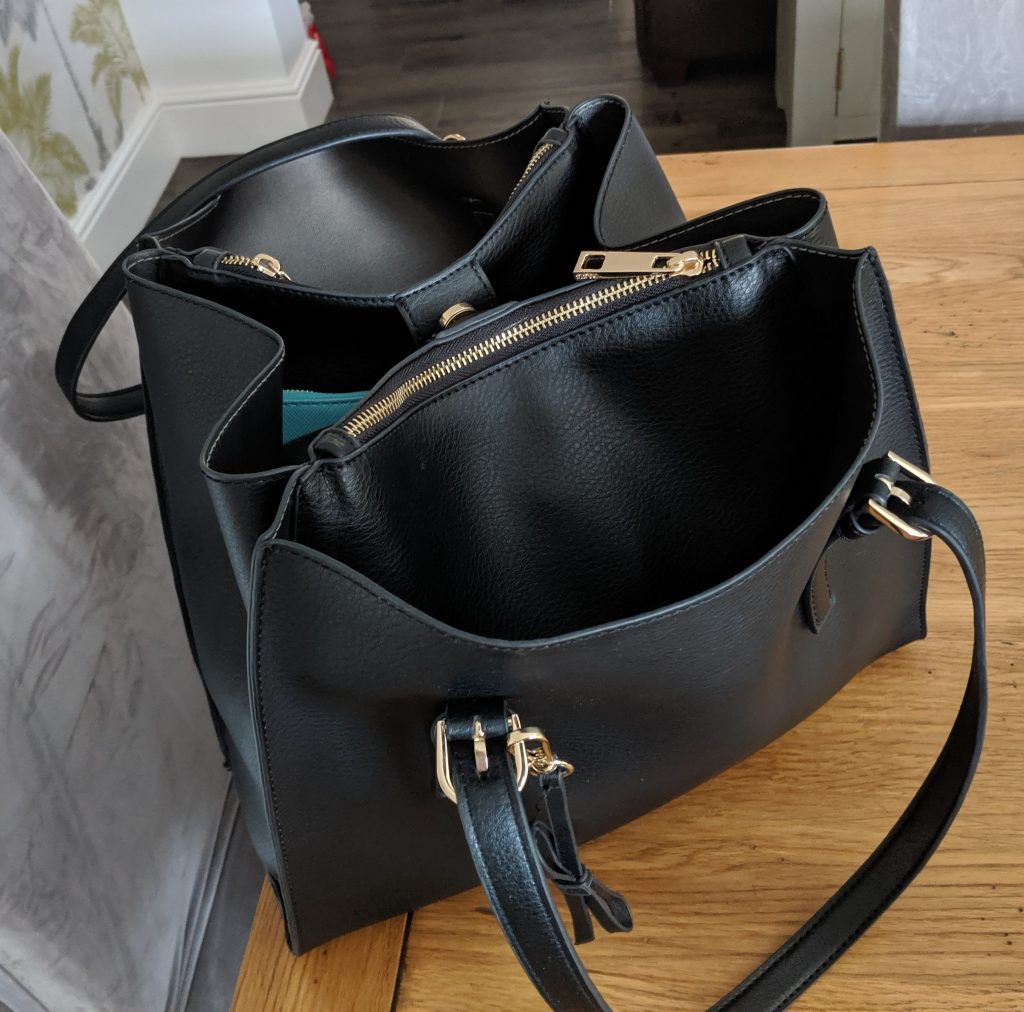 black handbag looking empty but used for overnight travel